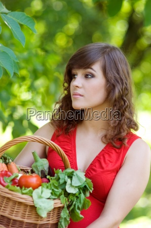 young woman holding basket filled vegetables