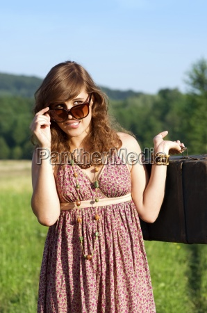 young woman looking behind sunglasses