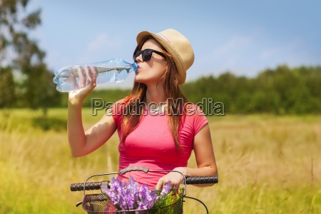 active woman with bike drinking cold