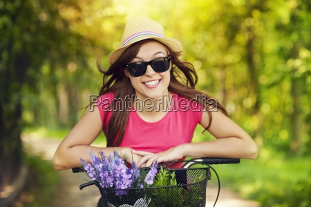 portrait of smiling woman riding bicycle