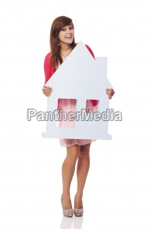 elegant young woman holding house sign