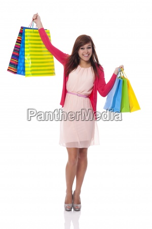 smiling young woman holding up shopping