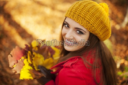 beautiful woman holding leaves in sunny