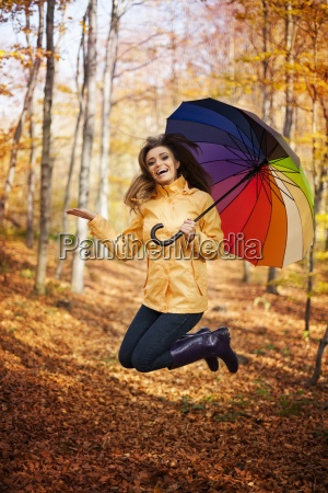 young woman jumping during the rainy