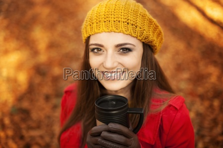 beautiful young woman drinking hot drink
