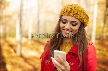 smiling woman using mobile phone in