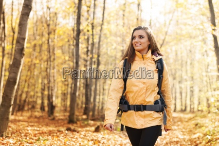 smiling woman wearing yellow jacket walking