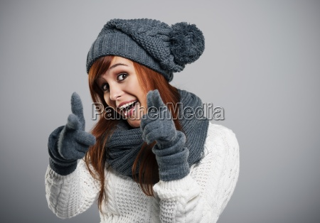 young woman wearing warm clothes pointing