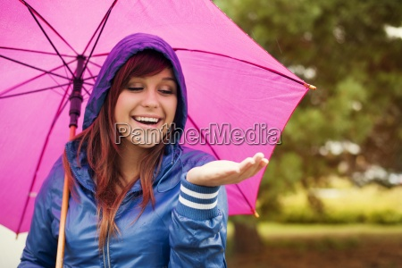 cheerful woman under pink umbrella checking