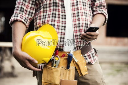 close up of construction worker texting