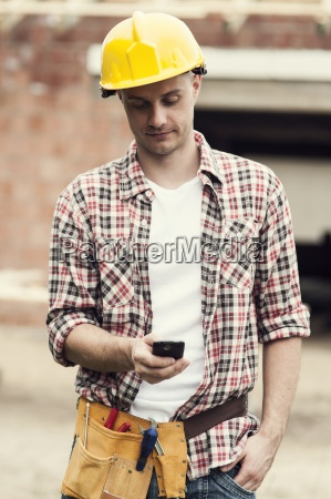 construction worker texting on mobile phone
