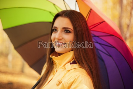 smiling, woman, standing, under, the, umbrella - 12110016