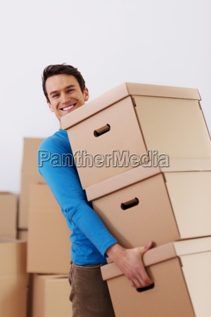handsome man carrying stack of boxes