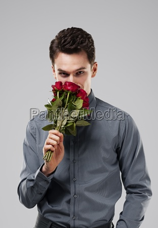 handsome man smelling bouquet of red