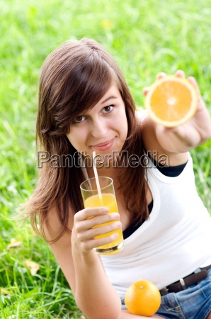 young woman holding orange and vitamin