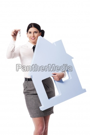 beautiful businesswoman holding house sign and