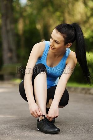 young woman tying sports shoe