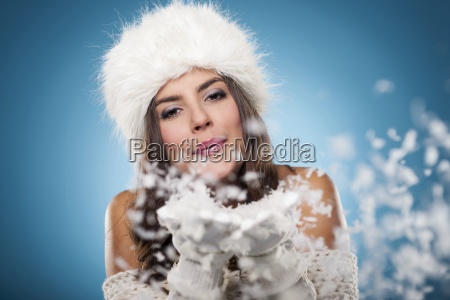 beautiful winter woman blowing snow