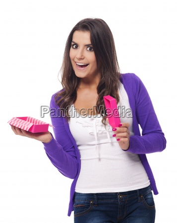 surprised woman opening small pink gift