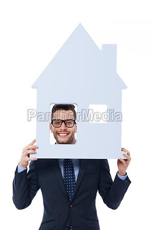 smiling businessman holding house sign