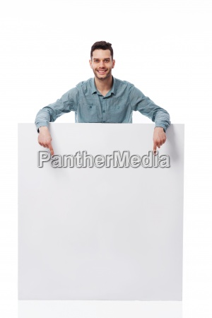 happy young man pointing at empty