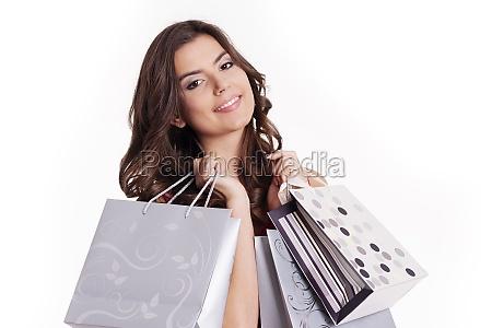 brunette woman holding shopping bags next