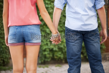 closeup of young couple holding hands