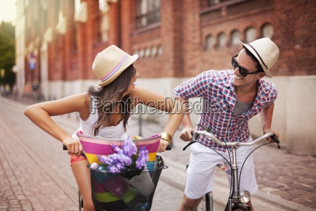 happy couple chasing on bike in