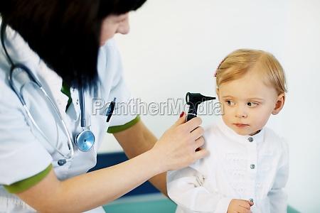 pediatrician doing ear exam of baby