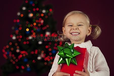 cute little girl holding christmas gift