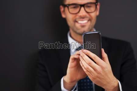 smiling businessman text messaging on smart