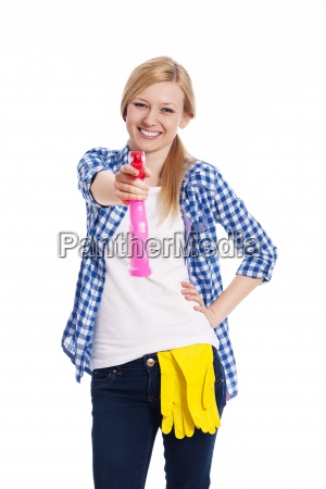 smiling woman spraying the cleaner on
