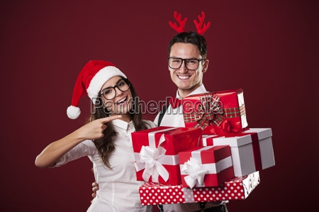 smiling nerd couple showing christmas gift