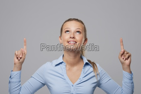 blonde businesswoman pointing above at copy