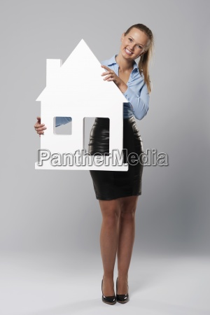 smiling young woman holding house sign