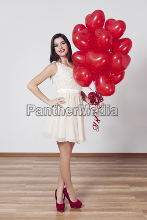 woman holding many balloons in heart