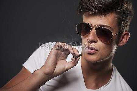 stylish young man smoking cigarette