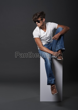 young fashion man sitting on white