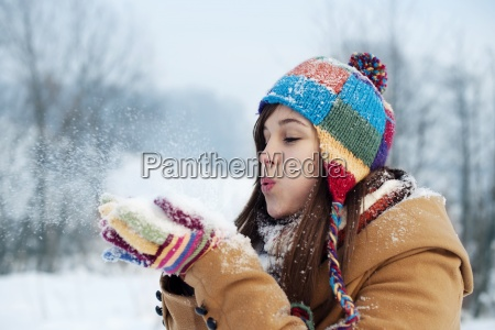 young woman blowing snow to away
