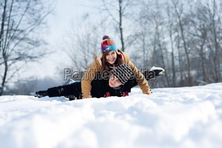 young couple sledding on snow