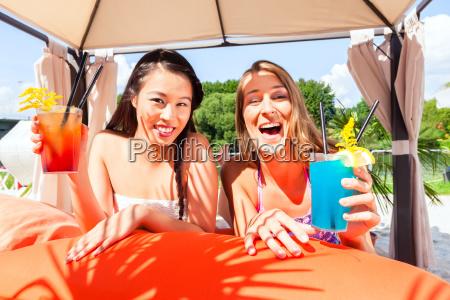 girlfriends drinking cocktails in bar beach