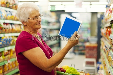 senior woman reading description on the