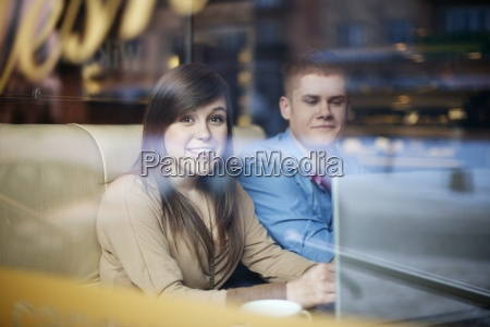 young couple using laptop in coffee