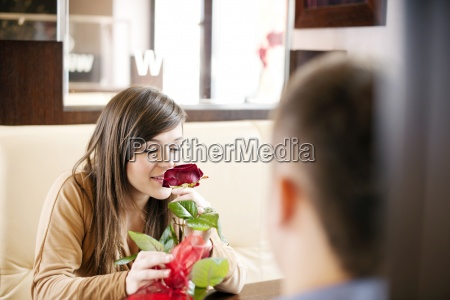 young man giving a rose his