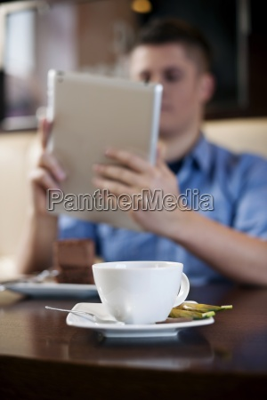 young man using tablet in coffee