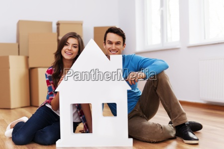 young couple with house sign