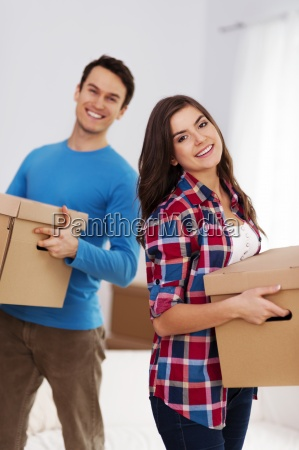 happy couple carrying boxes in their