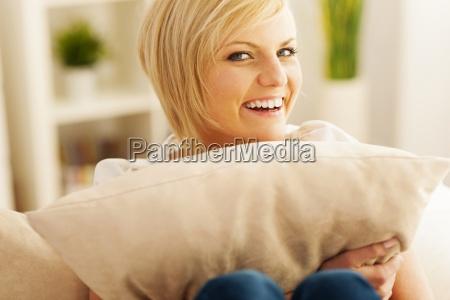 beautiful and smiling woman embracing pillow
