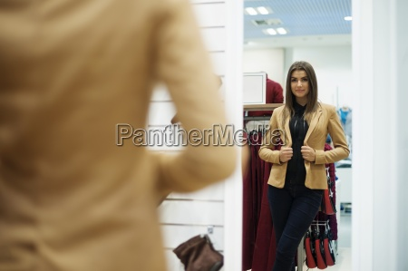 beautiful young woman trying on jacket