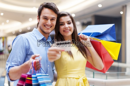 beautiful couple showing credit card in